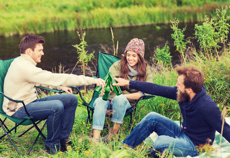 clinking: adventure, travel, tourism, friendship and people concept - group of smiling tourists clinking beer bottles in camping Stock Photo