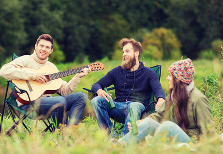 non alcoholic beer: adventure, travel, tourism and people concept - group of smiling tourists playing guitar and drinking beer in camping