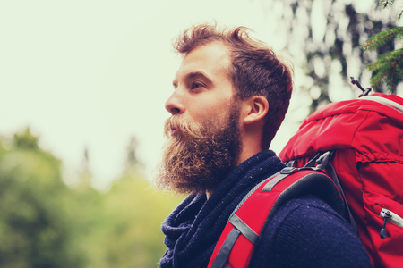 mochila de viaje: adventure, travel, tourism, hike and people concept - smiling man with beard and red backpack hiking