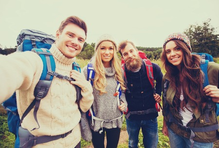 self discovery: adventure, travel, tourism, hike and people concept - group of smiling friends with backpacks making selfie outdoors Stock Photo