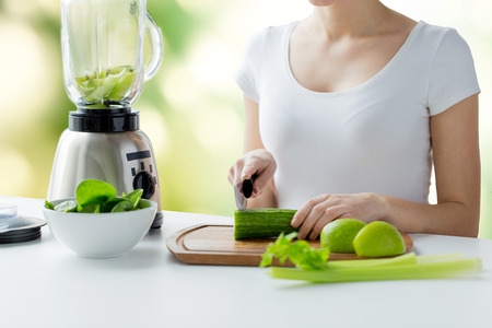 healthy eating, cooking, vegetarian food, dieting and people concept - close up of young woman with blender chopping green vegetables for detox shake or smoothie over natural background Archivio Fotografico