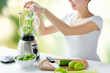 green vegetable: healthy eating, cooking, vegetarian food, dieting and people concept - close up of young woman with blender and green vegetables making detox shake or smoothie over natural background