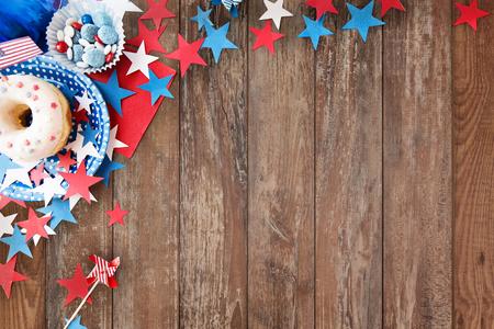 julio: día de la independencia americana, celebración, el patriotismo y el concepto de vacaciones - cerca de donut glaseado con los caramelos en vajillas desechables y las estrellas en el cuarto partido de julio desde la parte superior sobre fondo de madera