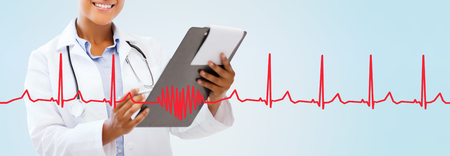 health care, people and medical concept - close up of smiling african american female doctor pointing finger to blank paper sheet on clipboard with red heart shape and cardiogram over blue background Stock Photo