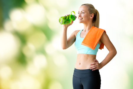 girl with towel: fitness, sport, training, drink and lifestyle concept - woman with bottle of water and towel over green natural background