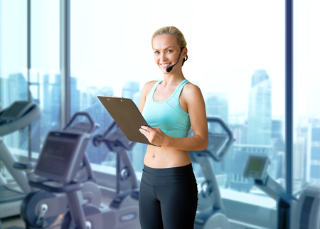 fitness, sport and people concept - happy woman sports trainer with microphone and clipboard over gym machines background