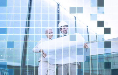 unwrapping: business, partnership, architecture and people concept - smiling businessman and businesswoman with blueprint and helmets over city street and blue grid background