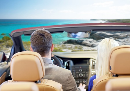 beach view: drive, auto trip, travel, tourism and people concept - close up of couple driving in cabriolet car from back over sea shore background