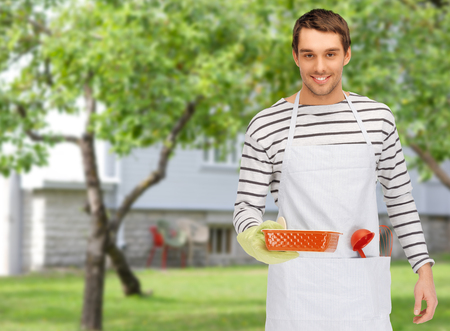 cook house: people, cooking, culinary and food concept - happy man or cook in apron with baking and kitchenware over summer garden and house background
