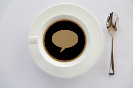 caffeine free: drinks, energetic, morning and communication concept - cup of black coffee with text bubble on surface, spoon and saucer on table