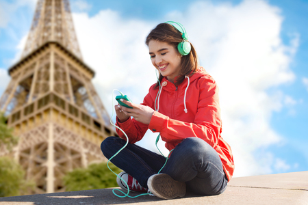 paris france: technology, travel, tourism and people concept - smiling young woman or teenage girl with smartphone and headphones listening to music over eiffel tower background