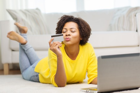 people, internet bank, online shopping, technology and e-money concept - happy african american young woman lying on floor with laptop computer and credit card at home Imagens