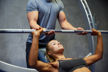 benches: sport, fitness, teamwork, bodybuilding and people concept - young woman and personal trainer with barbell flexing muscles in gym