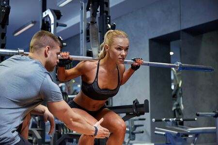 sport, fitness, teamwork, bodybuilding and people concept - young woman and personal trainer with bar flexing muscles in gym Stock Photo