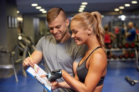 cheque en blanco: fitness, deporte, ejercicio y dieta concepto - mujer joven con entrenador personal y plan de ejercicios en el sujetapapeles en el gimnasio sonriente