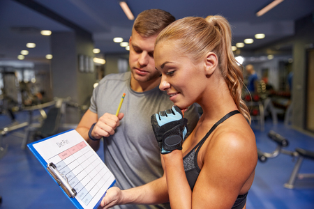 personal trainer: fitness, sport, exercising and diet concept - smiling young woman with personal trainer and exercise plan on clipboard in gym