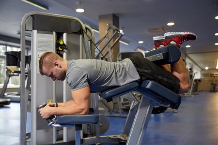sport, fitness, kulturystyka, styl życia, a ludzie koncepcji - człowiek sprawowanie i wyginanie mięśnie nóg zwinięcie maszynie w siłowni