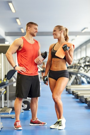 sport, fitness, style de vie et les gens concept - homme et femme avec une bouteille de protéines shake et serviette parler dans le gymnase en souriant