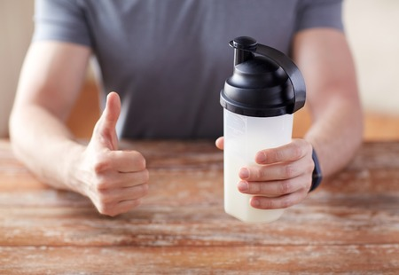 shake up: sport, fitness, healthy lifestyle and people concept - close up of man in fitness bracelet with protein shake bottle showing thumbs up