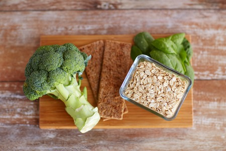 rich life: healthy eating, diet and fiber rich in food concept - close up of broccoli, crispbread, oatmeal and spinach on wooden table