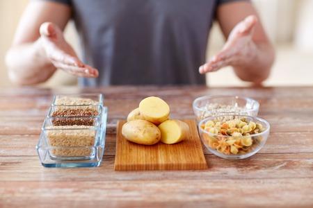 건강한 식습관, 다이어트 사람들 개념 - 가까운 남성의 손에의 닫 테이블에 탄수화물 음식을 보여주는