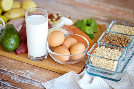 balanced diet, cooking, culinary and food concept - close up of eggs, cereals and milk glass on wooden table