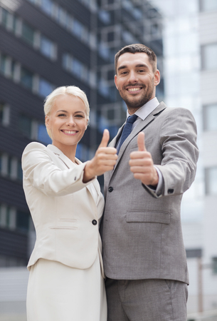 co workers: business, partnership, success, gesture and people concept - smiling businessman and businesswoman showing thumbs up over office building Stock Photo