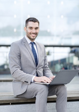 learning online: business, education, technology and people concept - smiling businessman working with laptop computer on city street