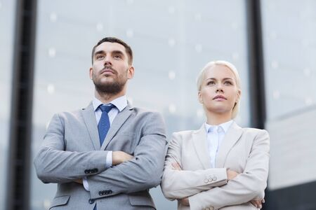 businesspeople: business, partnership, success and people concept - serious businessman and businesswoman standing over office building