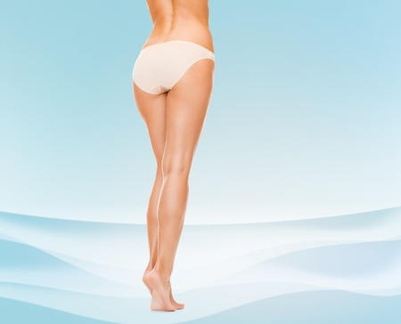 cotton panties: people, health and beauty concept - woman with long legs in cotton panties from back over blue background