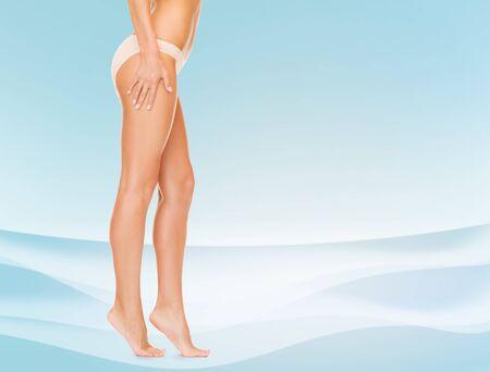 piernas mujer: las personas, la salud y el concepto de belleza - mujer con las piernas largas en bragas de algodón que toca sus caderas y caminar de puntillas sobre fondo azul Foto de archivo