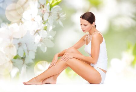 girl  care: people, beauty and body care concept - beautiful woman in cotton underwear touching legs over green natural cherry blossom background Stock Photo