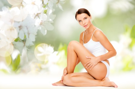 beautiful woman body: people, beauty and body care concept - beautiful woman in cotton underwear touching her hips over green natural cherry blossom background