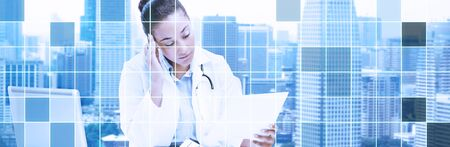 grid paper: health care, medicine, people and technology concept - african american female doctor with laptop reading medical report paper over city and blue monochrome grid background Stock Photo