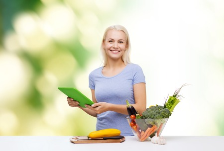 food technology: healthy eating, cooking, vegetarian food, technology and people concept - smiling young woman with tablet pc computer and bowl of vegetables over green natural background Stock Photo