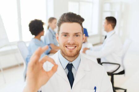 emergencia medica: clínica, la profesión, el gesto, la gente y concepto de la medicina - doctor de sexo masculino feliz que muestra la muestra de la mano bien sobre el grupo de médicos de reuniones en el hospital Foto de archivo