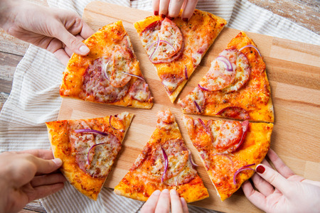 food, italian kitchen and eating concept - close up of hands taking and sharing homemade pizza on wooden table