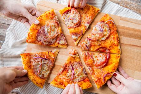 Konzept Essen, italienische Küche und Essen - in der Nähe der Hände nach oben zu nehmen und teilen hausgemachte Pizza auf Holztisch