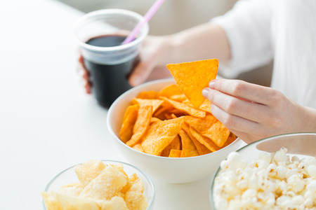 drink food: people, fast food, junk-food and unhealthy eating concept - close up of woman with popcorn, nachos or corn crisps and peanuts in bowls