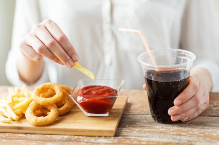 salsa de tomate: comida rápida, las personas y el concepto de alimentación poco saludable - cerca de la mujer con los anillos de calamar fritos, patatas fritas inmersión en un tazón de salsa de tomate y coca cola potable en mesa de madera Foto de archivo