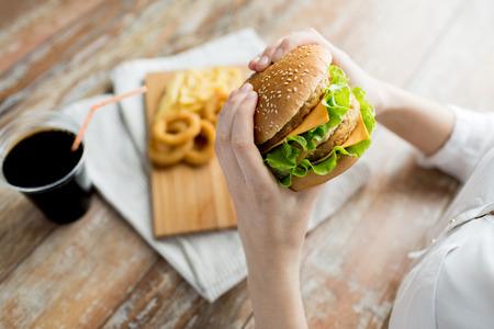 comida rapida: comida rápida, las personas y el concepto de alimentación poco saludables - primer plano de manos de la mujer la celebración de hamburguesa o hamburguesa Foto de archivo
