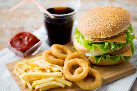 comida rápida y el concepto de alimentación poco saludable - cerca de la hamburguesa o hamburguesa, anillos de calamar fritos, patatas fritas, refresco de cola y salsa de tomate en la mesa de madera Foto de archivo