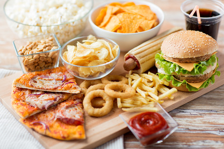 food menu: fast food and unhealthy eating concept - close up of fast food snacks and cola drink on wooden table