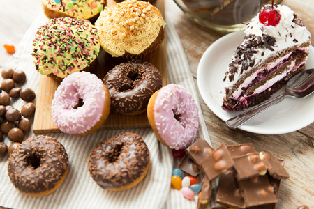 junk food, culinary, baking and eating concept - close up of glazed donuts, cakes and chocolate sweets on table Foto de archivo