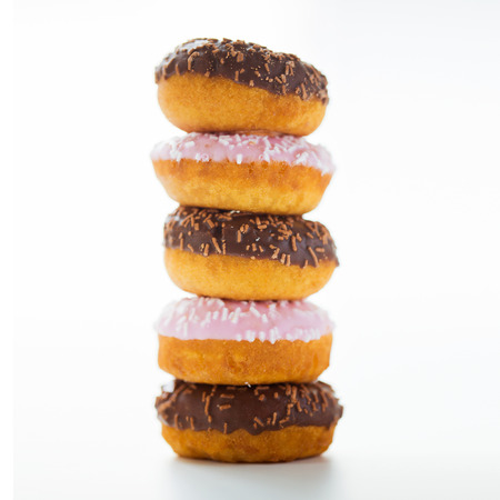 food, junk-food and eating concept - close up of glazed donuts pile over white 版權商用圖片