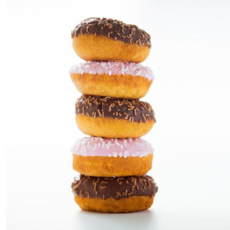 food, junk-food en eten concept - close-up van geglazuurde donuts stapel op witte