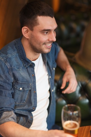 beerhouse: people, drinks, alcohol and leisure concept - happy young man drinking beer at bar or pub Stock Photo