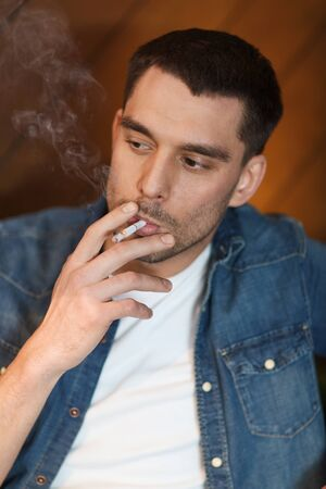 bad habit: people and bad habits concept - young man smoking cigarette at bar Stock Photo