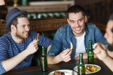 bottled: people, leisure, friendship and bachelor party concept - happy male friends drinking bottled beer and talking at bar or pub