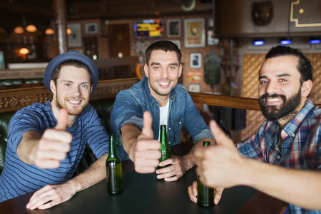 people, leisure, friendship, gesture and bachelor party concept - happy male friends drinking bottled beer and showing thumbs up at bar or pub Foto de archivo